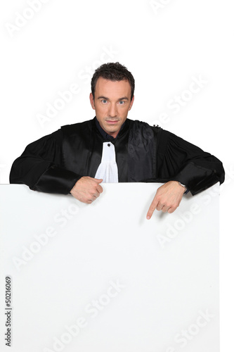 Man in black robes pointing at a board left blank for message