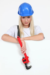 Woman stood by blank poster holding wrench