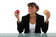 Woman choosing between apple and burger