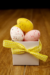 Miniature coloured eggs in a white box