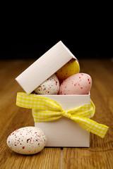Miniature coloured eggs in a white box