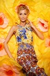 Beautiful young blond woman in colourful dress lying among big y
