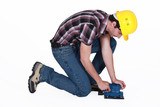 Workman using an electric sander poster