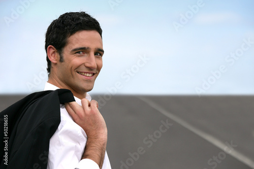 Businessman stood on empty road