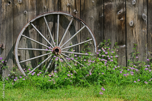 Wooden Wheel against Barn Wall