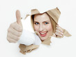 Pretty woman with thumb up looking through paper hole