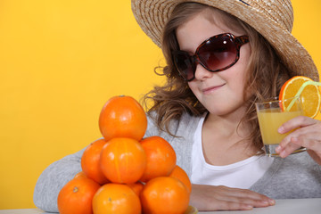 Girl in sunglasses with fresh orange juice