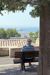 Old man sat on a bench by the coast
