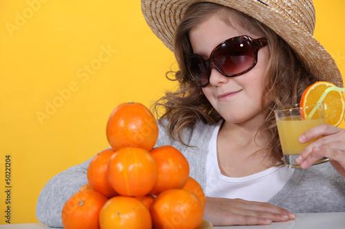 Girl in sunglasses with fresh orange juice