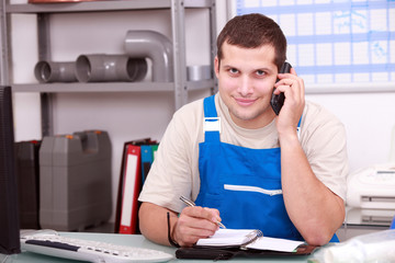 Plumbers' merchant taking a phone call