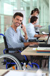 Smiling man in a wheelchair working in an office