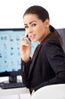 Business woman talking phone while sitting in front of computer