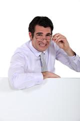Doubtful man peering over his glasses