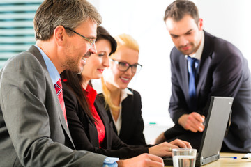 Businesspeople looking at laptop screen