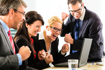 Business people looking at laptop with success