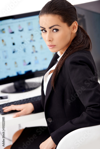 Woman in black suit sitting in front of computer