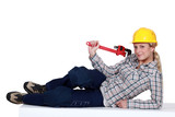 Attractive blond plumber laying with wrench