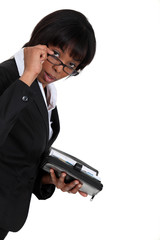 black businesswoman with lowered glasses holding agenda
