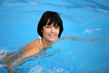 Brunette swimming in pool