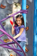 Girl On Climbing Frame In Park
