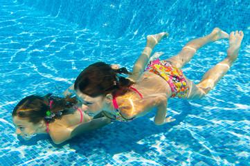Underwater kids in swimming pool, girls swim and having fun