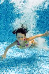 Underwater child in swimming pool, girl swims and having fun