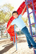 Boy On Climbing Frame In Park