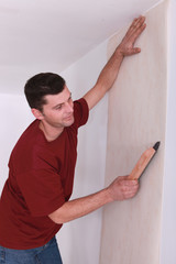 man wallpapering