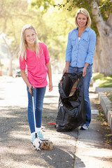 Mother And Daughter Picking Up Litter In Suburban Street