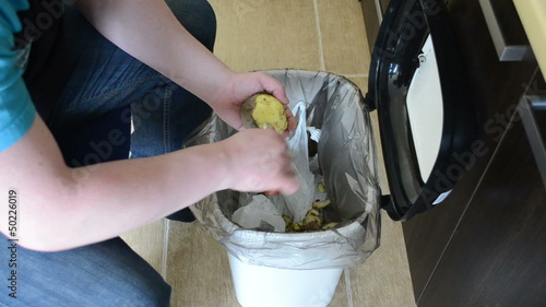 hands peel potatoes. paring fall into recycle bin