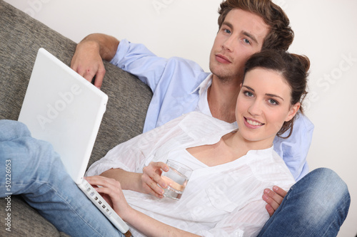 Couple sat with their laptop computer