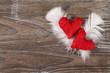 Zwei rote Herzen mit Federn  auf Holzuntergrund