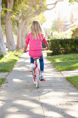 Girl Riding Bike Along Path
