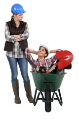 craftswoman accusing her colleague for sitting in wheelbarrow