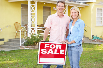 Couple Standing By For Sale Sign Outside Home