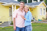 Couple Standing Outside Suburban Home