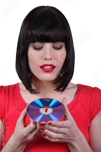 Dark -haired woman holding compact disc in hands