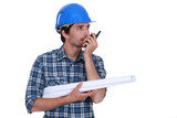 Engineer with plans and a walkie talkie