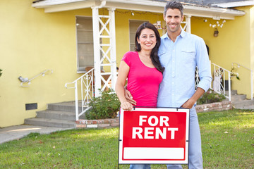 Couple Standing By For Rent Sign Outside Home