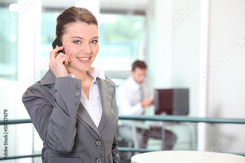 Young businesswoman making a call in the office