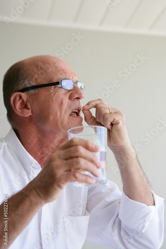 Senior man taking his medicine