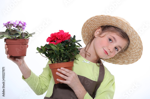 9 years old girl dressed in horticulturist taking flower pots