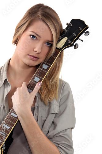 Blond teenage girl posing with guitar