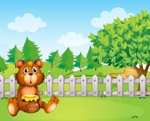 A bear inside the fence holding a pot of honey