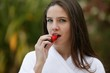Young brunette eating strawberry