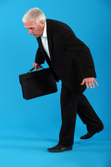 Senior businessman walking invisible tight rope