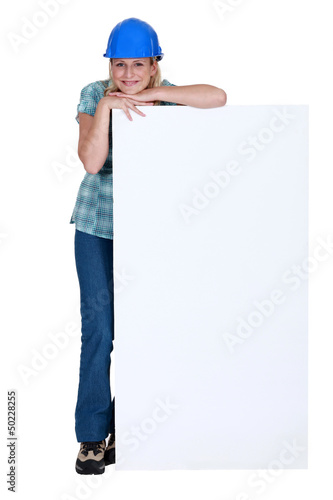 Woman with protective helmet leaning on a white sign