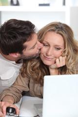 Husband kisses wife on the cheek.