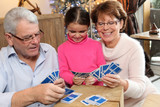 Little girl playing cards with her grandparents