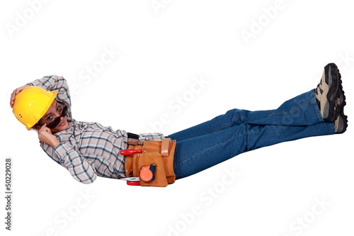 Female builder in sunglasses laying down